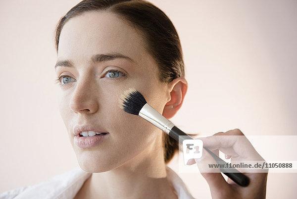 Woman having makeup applied by stylist