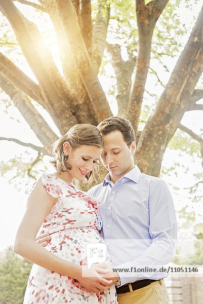 Pregnant Caucasian couple hugging outdoors
