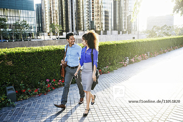 Smiling business people talking and walking outdoors
