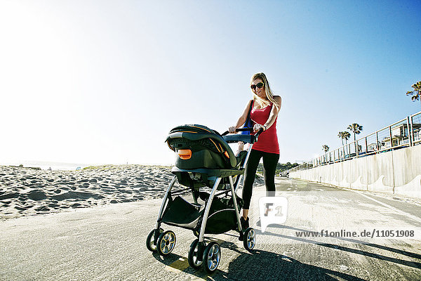 Mother pushing baby son in stroller at beach
