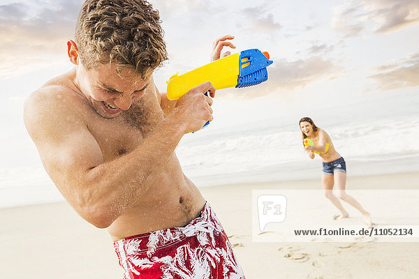 Caucasian couple playing with squirt guns on beach