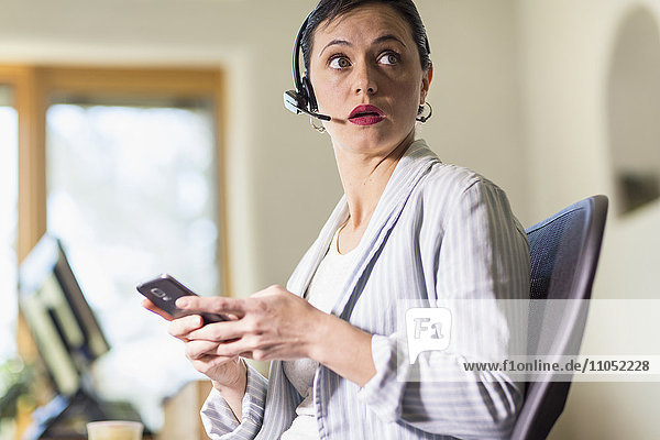 Businesswoman using cell phone and headset in office