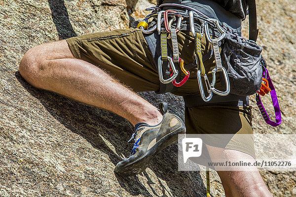 Carabiners on Caucasian man climbing rock