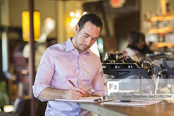 Hispanic businessman writing on clipboard in coffee shop