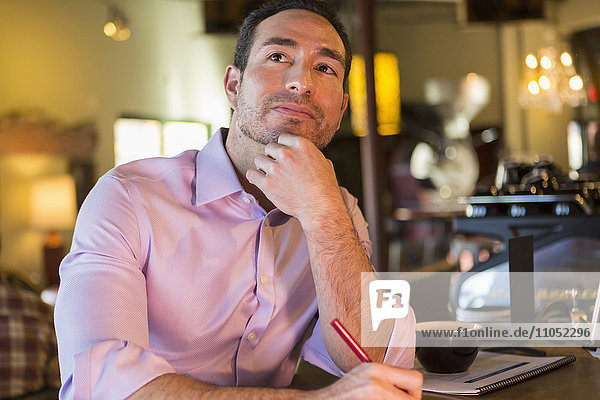 Hispanic businessman working in coffee shop