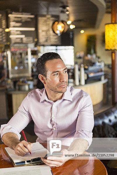 Hispanic businessman using cell phone in coffee shop