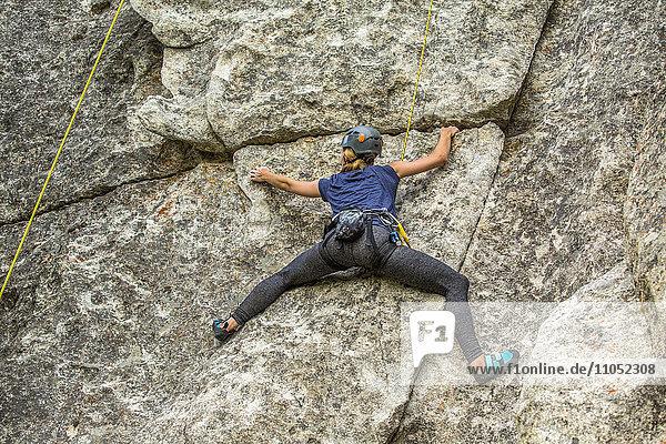 Caucasian woman climbing rock