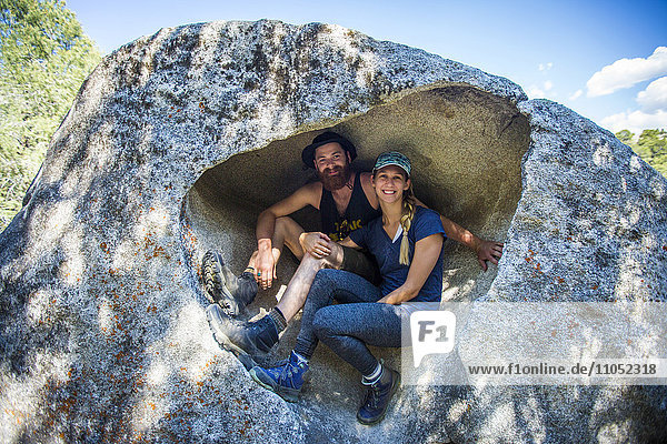 Caucasian couple sitting in rock formation