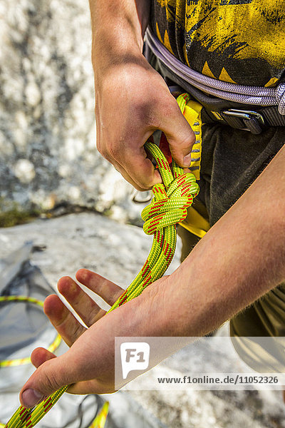 Caucasian rock climber fastening rope to harness