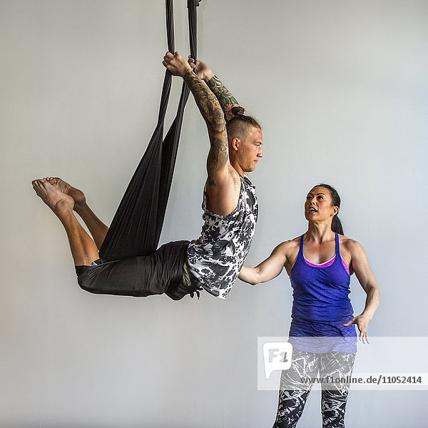 Mixed Race instructor assisting student hanging from silks