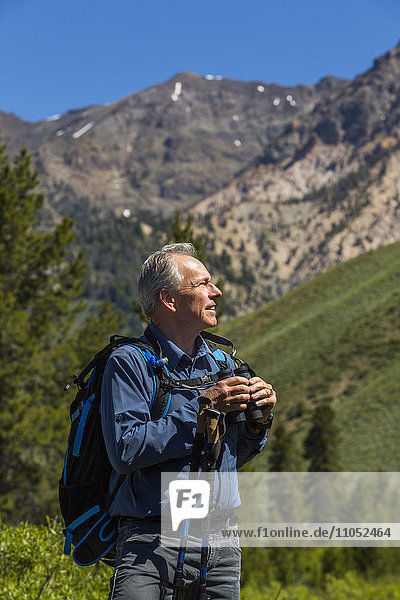 Caucasian man hiking in mountains with binoculars