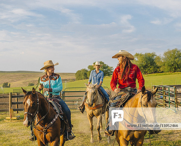Cowgirls riding horseback on ranch