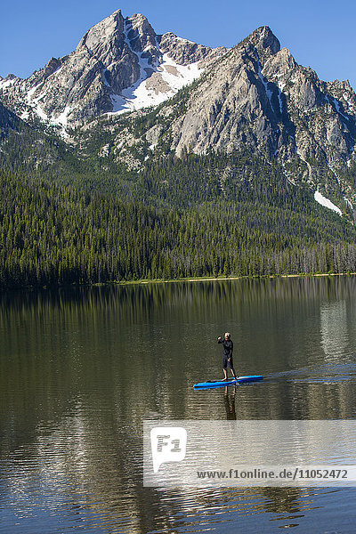 Caucasian man on paddleboard on mountain lake