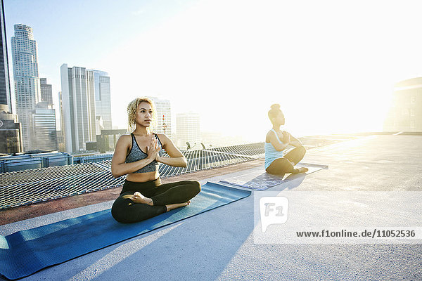 Women practicing meditating on urban rooftop