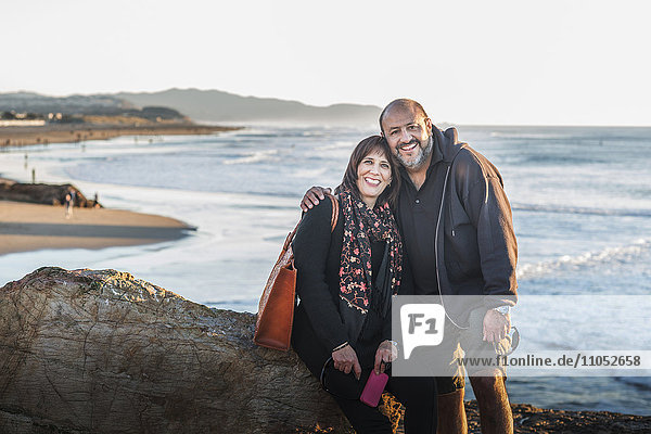 Hispanic couple hugging on beach