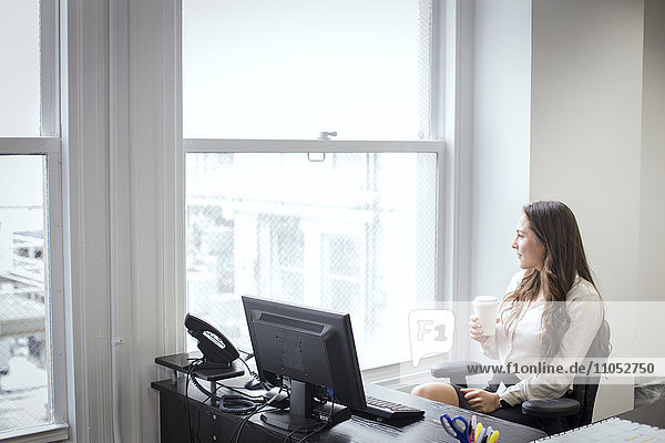 Caucasian businesswoman looking out office window