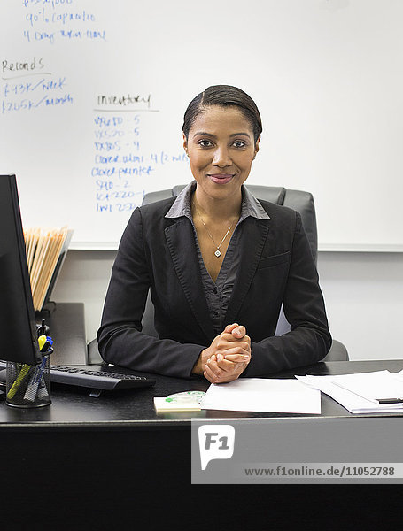 African American businesswoman sitting at desk in office