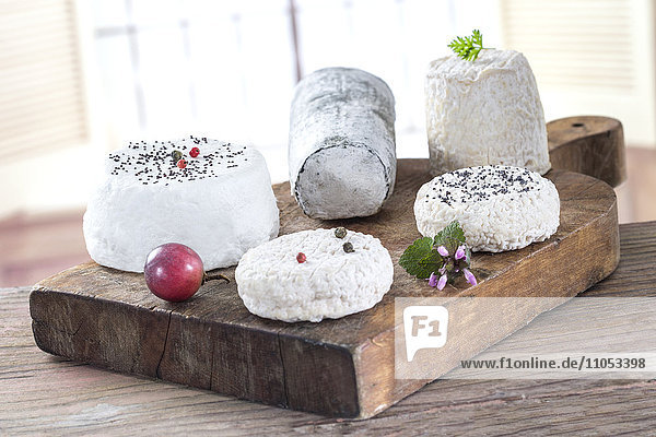 Various french goat cheese on wooden board.