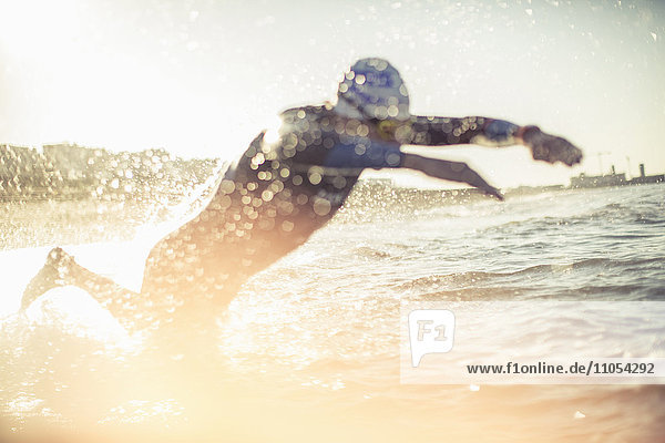 A swimmer in a wet suit running into the water  making a splash.