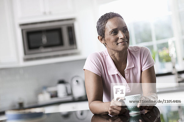A woman leaning on the smooth countertop of her kitchen unit  with a cup of coffee.