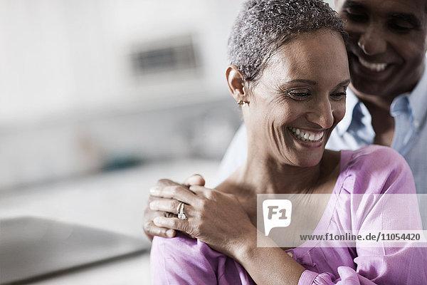 Ein liebevolles,  reifes afroamerikanisches Ehepaar,  das sich in ihrem Haus umarmt.