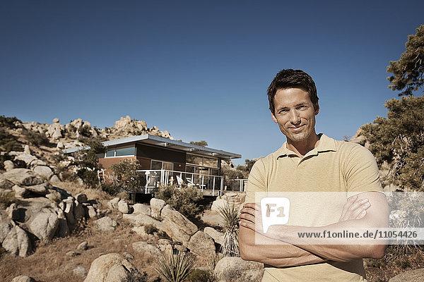 Ein Mann steht vor einem Ökohaus  das sich in die felsige Hügellandschaft einer Wüstenlandschaft einfügen soll. Nachhaltige Architektur mit geringen Auswirkungen.