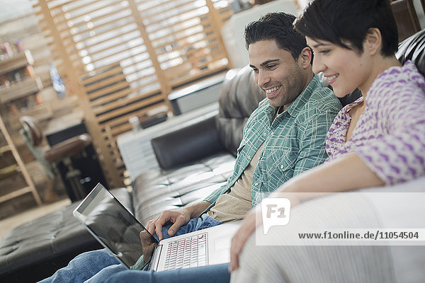 A man and woman sitting on a sofa  looking at the screen of a laptop.
