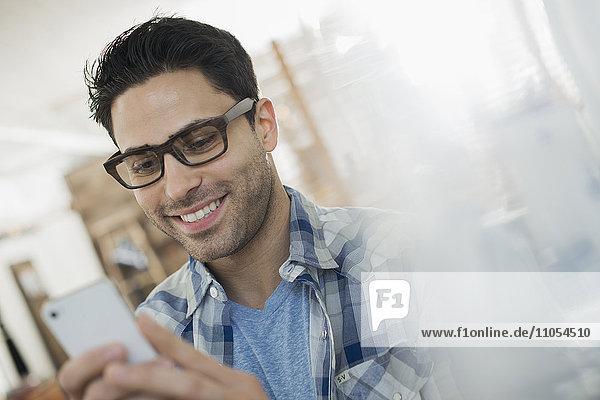 Ein Mann überprüft sein Smartphone.