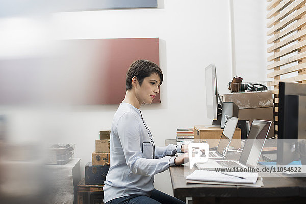 A woman in a home office seated at a desk with two laptops  her hands on the keyboard of one computer  looking at the screen on the other.