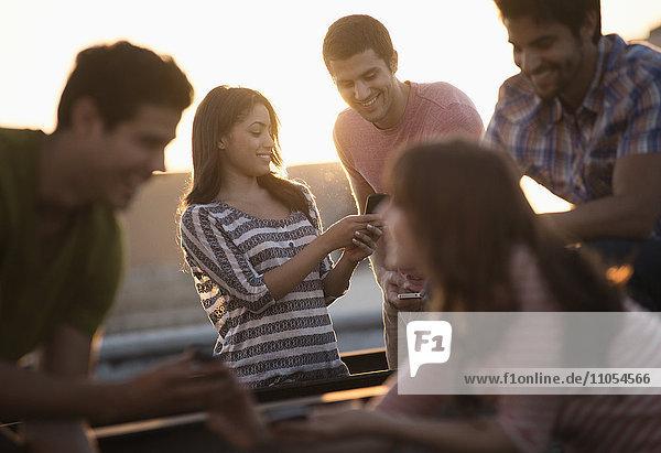 Eine Gruppe von Männern und Frauen feiert auf einer Dachterrasse eine Party.