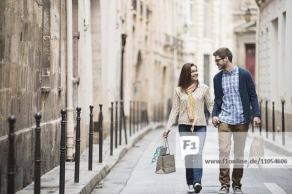 Ein Paar,  das mit Einkaufstaschen durch eine schmale Stadtstraße läuft.