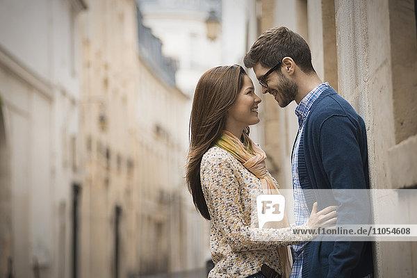 Ein Paar  das sich in einer engen Straße in einer Stadt gegenseitig anstarrt.