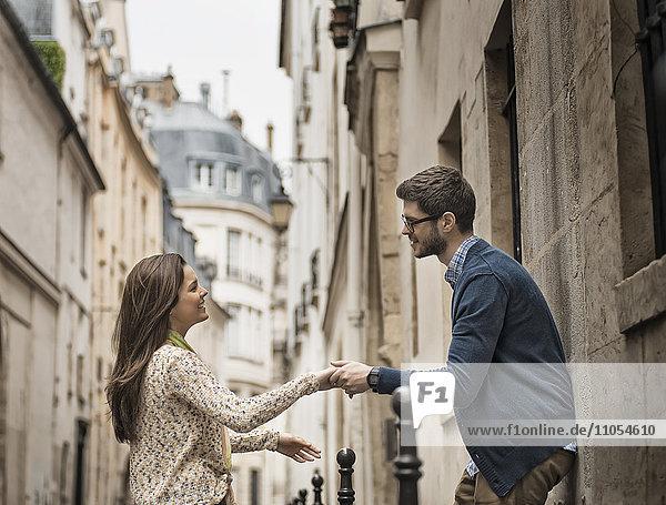 Ein Mann und eine Frau halten sich auf einer Straße in der Stadt an den Händen.