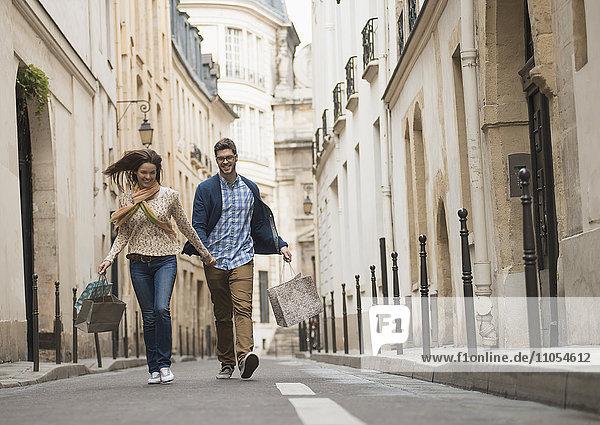 Ein Paar  das mit Einkaufstaschen durch eine schmale Straße in einem historischen Stadtzentrum geht.
