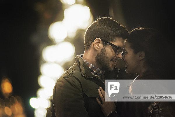 Ein Paar  das sich nachts in einer Stadt umarmt und küsst.