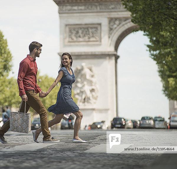 Ein Paar  das Hand in Hand Einkaufstaschen trägt und die Straße an einem historischen Denkmal im Herzen einer europäischen Stadt überquert.