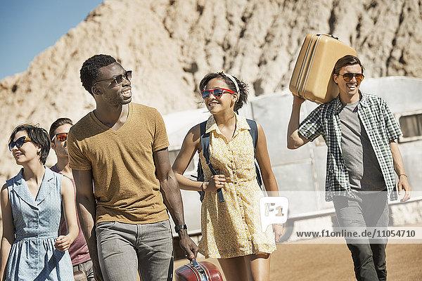 Eine Gruppe von Menschen  die mit ihren Koffern in einer Schlange in einem offenen Wüstenland unterwegs sind.