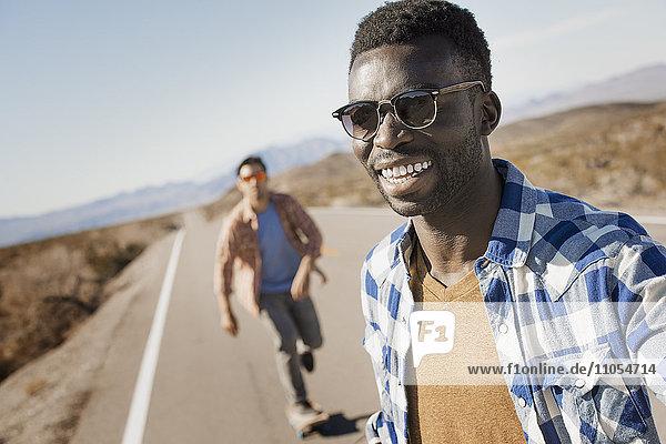 Zwei Männer auf einer asphaltierten Straße in freier Natur.