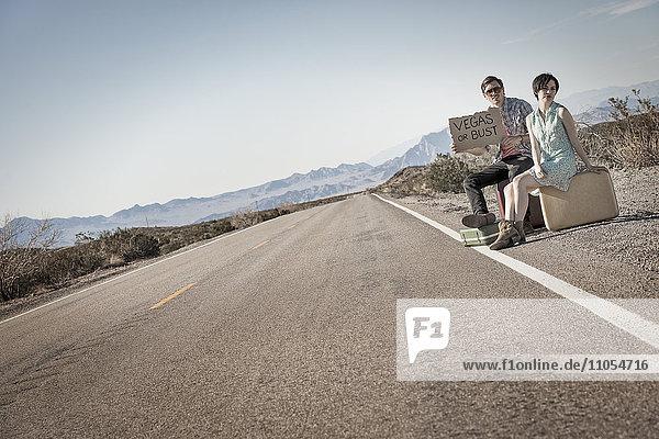 Ein junges Paar  Mann und Frau  auf einer asphaltierten Straße in der Wüste beim Trampen  mit einem Schild mit der Aufschrift Vegas oder Bust.
