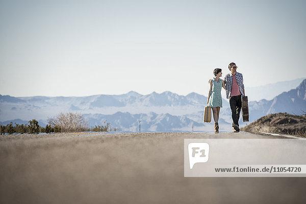 Ein junges Paar  Mann und Frau  auf einer asphaltierten Straße in der Wüste mit Koffern.