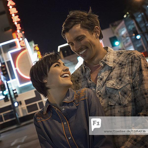 Ein Paar  Mann und Frau Seite an Seite in einer nächtlichen Straße der Stadt. Neonschilder.