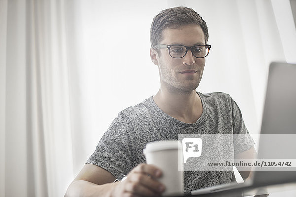 A working day. A man seated at a laptop computer  working in a hotel bedroom with a cup of coffee.