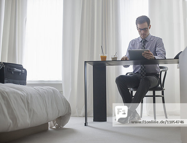 A working day. A man seated at a laptop computer  working in a hotel bedroom.