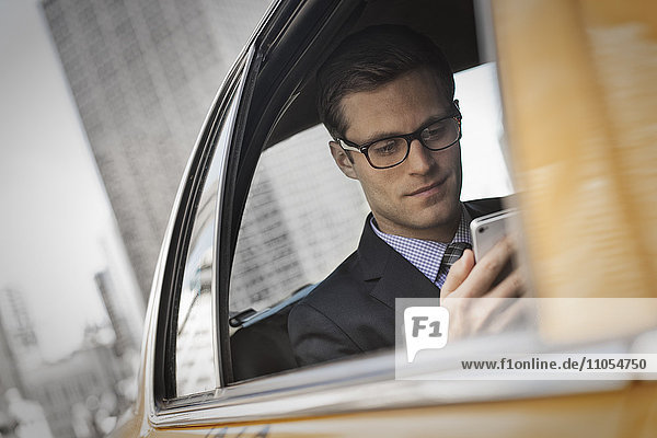 A working day. Businessman in a work suit sitting in a cab checking his phone.
