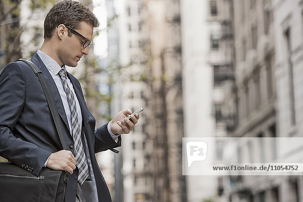 A working day. Businessman in a work suit and tie on a city street  using his phone.