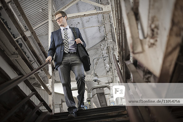 A working day. Businessman in a work suit and tie walking down stairs in a public space.