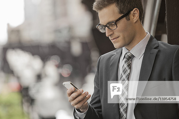 A working day. Businessman in a work suit and tie on a city street  looking at his phone.
