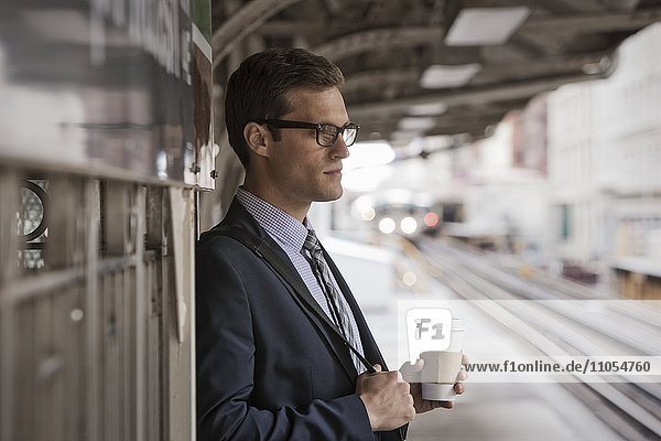 A working day. Businessman in a work suit and tie holding a cup of coffee on a railway platform.