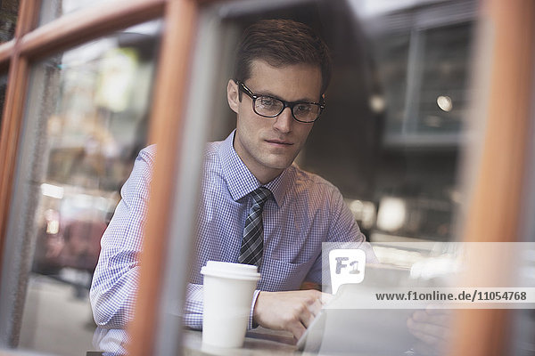 A working day. Businessman sitting in a cafe  using laptop  having coffee.