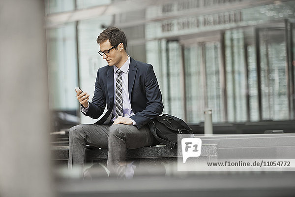 A working day. Businessman in a work suit and tie sitting checking his phone.